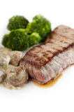 Grilled steak. On a white plate with mushroom sauce and broccoli Royalty Free Stock Image