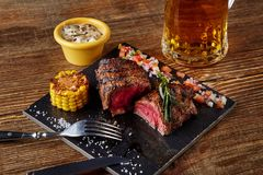 Free Grilled Steak With Corn With Mushrooms Sauce On Cutting Board And Mug Of Beer On Wooden Table Stock Photo - 107437230