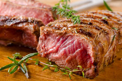 Grilled  steak on   wooden cutting board . Stock Photography