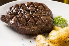 Grilled steaks, baked potatoes and vegetable salad Stock Photo