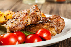 Grilled steaks, baked potatoes and vegetables Royalty Free Stock Photos