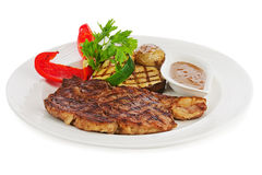 Grilled steaks, baked potatoes and vegetables on white plate. Stock Photo