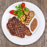 Grilled steaks, baked potatoes and vegetables on white plate on Royalty Free Stock Photos
