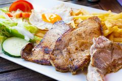 Grilled steaks, French fries, fried egg Royalty Free Stock Images
