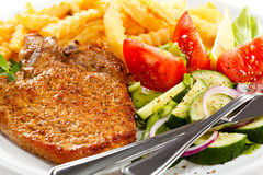 Grilled steaks and French fries Stock Photos