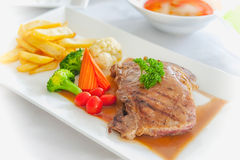 Grilled steaks, French fries and vegetables Royalty Free Stock Photo