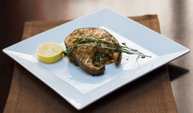 Grilled steaks of fresh fish with lemon and rosemary Stock Image