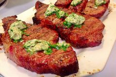 Grilled Steaks with Herb Butter. Grilled Beef Steaks with Herb Butter on a white platter stock image
