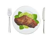 Grilled steaks and lime slices on plate isolated on white Stock Photo