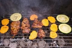 Grilled steaks and vegetables like sweet potatoes and zucchini cooked on the garden grill. Royalty Free Stock Image