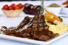 Grilled steaks and vegetables. Grilled meat with barbecue sauce and vegetable salad stock photography