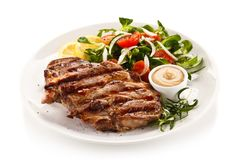 Grilled steaks and vegetables stock photography