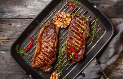 Grilled  strip steak with spices. Grilled  striploin steak with spices and herbs on grill iron pan.The strip steak, also called a New York strip Stock Image