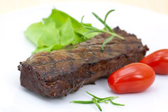 Grilled strip steak with tomato and salad stock images