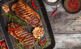 Grilled strip steak with spices. Grilled striploin steak with spices and herbs on grill iron pan.The strip steak, also called a New York strip Stock Photography