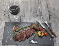 Grilled striploin steak on a stone plate with a glass of red wine with a fork and knife. Royalty Free Stock Images