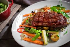 Grilled Juicy Striploin beef steak with vegetables on plate stock photos