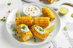 Grilled sweet corn with white mexican sauce, chilli and lime. healthy summer food royalty free stock photo