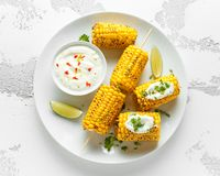 Grilled sweet corn with white mexican sauce, chilli and lime. healthy summer food royalty free stock photography