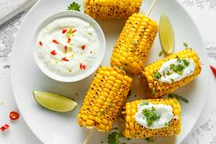 Grilled sweet corn with white mexican sauce, chilli and lime. healthy summer food stock photography