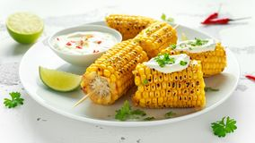 Grilled sweet corn with white mexican sauce, chilli and lime. healthy summer food stock photos