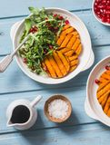 Grilled sweet potato and arugula salad - delicious vegetarian snack on blue background Stock Images