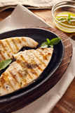 Grilled swordfish. Slices in a cast iron pan on a wooden table, garnished with mint, oregano, salt and salmoriglio Stock Images