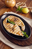 Grilled swordfish. Slices in a cast iron pan on a wooden table, garnished with mint, oregano, salt and salmoriglio Royalty Free Stock Photo