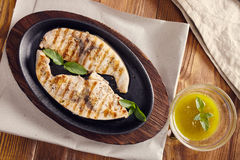 Grilled swordfish. Slices in a cast iron pan on a wooden table, garnished with mint, oregano, salt and salmoriglio Stock Photography