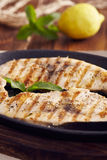 Grilled swordfish. Slices in a cast iron pan on a wooden table, garnished with mint, oregano, salt and salmoriglio Royalty Free Stock Photos