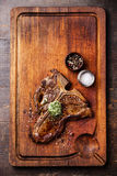 Grilled T-Bone Steak with herb butter. And salt and pepper on wooden cutting board Royalty Free Stock Photo