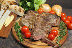 Grilled T bone steak with rosemary tomatoes, corn, onions and as Royalty Free Stock Photos