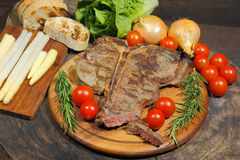 Grilled T bone steak with rosemary tomatoes, corn, onions and as Royalty Free Stock Photo
