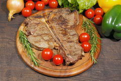 Grilled T bone steak with rosemary, tomatoes, corn, onions and Royalty Free Stock Image