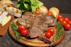 Grilled T bone steak with rosemary, tomatoes, corn, onions and Stock Photos