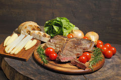Grilled T bone steak with rosemary, tomatoes, corn, onions and Royalty Free Stock Photo