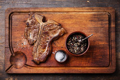 Grilled T-Bone Steak with salt and pepper. On meat cutting board on dark wooden background Stock Photo