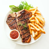 Grilled t-bone steak seasoned with rosemary. Grilled t-bone or porterhouse steak seasoned with rosemary and served with golden French fries, fresh leafy herb Stock Images