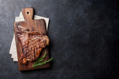 T-bone steak. Grilled T-bone steak on stone table. Top view with copy space Royalty Free Stock Photo