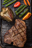 Grilled T-Bone Steak and Vegetables. Summer grill - grilled T-bone steak and assorted grilled vegetables - asparagus, mini pepper, and tomatoes - on griddle Royalty Free Stock Photo