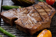 Grilled T-Bone Steak and Vegetables. Summer grill - grilled T-bone steak and assorted grilled vegetables - asparagus, mini pepper, and tomatoes - on griddle Royalty Free Stock Images