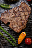 Grilled T-Bone Steak and Vegetables. Summer grill - grilled T-bone steak and assorted grilled vegetables - asparagus, mini pepper, and tomatoes - on griddle Royalty Free Stock Photography