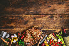 Grilled T-bone steaks with fresh herbs, vegetables ans wine bott royalty free stock photography