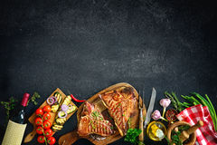 Grilled T-bone steaks with fresh herbs and vegetables stock photography
