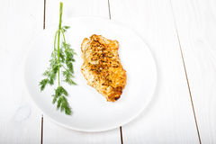 Grilled tasty chicken breasts on a white plate with fresh herbs Stock Photos