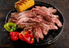 Grilled flank steak thinly sliced on a plate royalty free stock image