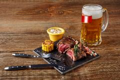 Grilled tenderloin Steak roastbeef and mushrooms sauce on black cutting board and glass of beer on wooden background. Serving a ready meal in a restaurant royalty free stock images
