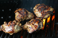 Grilled Tequila Lime Chicken. Grilled chicken thighs that were first marinated in lime and tequila; fire and smoke surrounding chicken Stock Photos