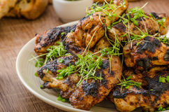 Grilled teriyaki chicken wings. With chive and microgreens on top, garlic toast with fresh herbs and czech beer Stock Image