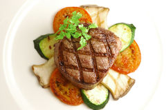 Grilled Thick Filet. Mignon served with king oyster and tomatos Stock Image